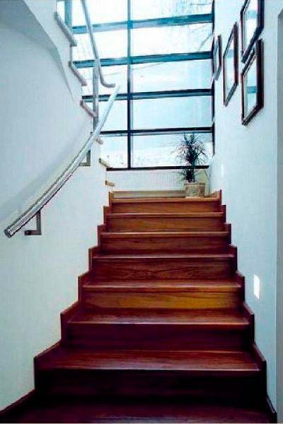 Лестницу с прямым маршем можно отделать практически любым материалом. В этом случае применена темная древесина, контрастирующая с цветом стен