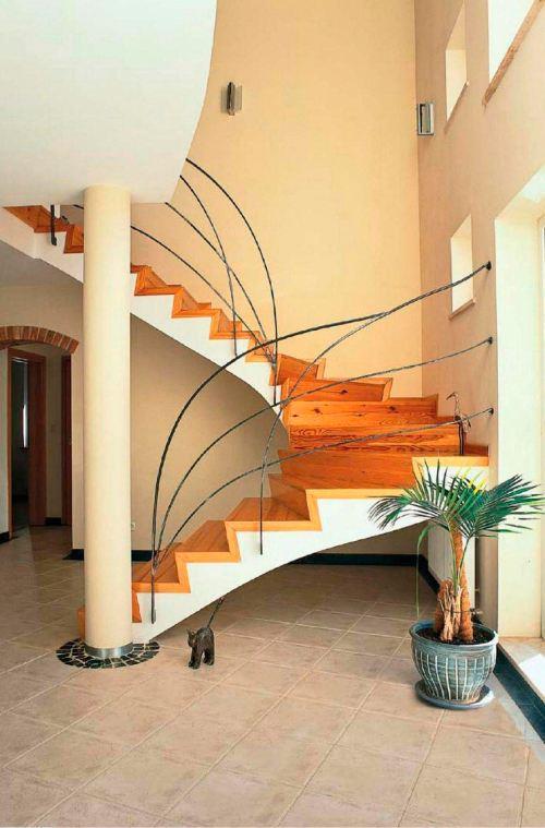 Лестница с несущей железобетонной конструкцией покрыта натуральной древесиной светлого тона. Благодаря этому винтовой марш выглядит легким и нарядным
