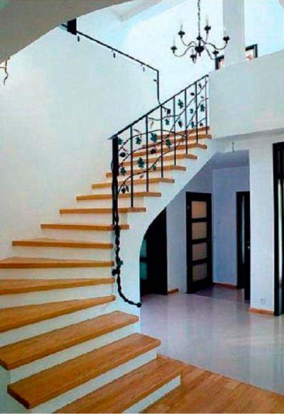 За счет подступенков, покрашенных в белый цвет, лестница с деревянными ступенями кажется легче