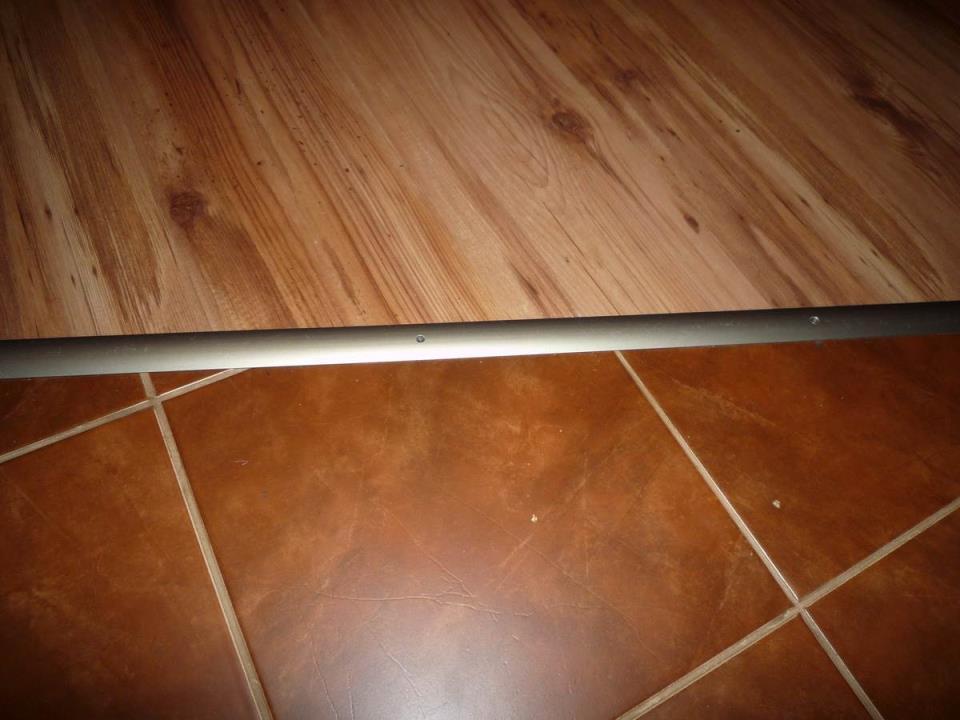 вариант использования гибкого порога для ламината и плитки в отделке дома