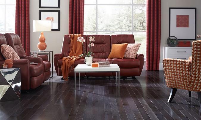 Интерьер с красно-коричневой мебелью и ламинированным полом с двухсторонней фаской