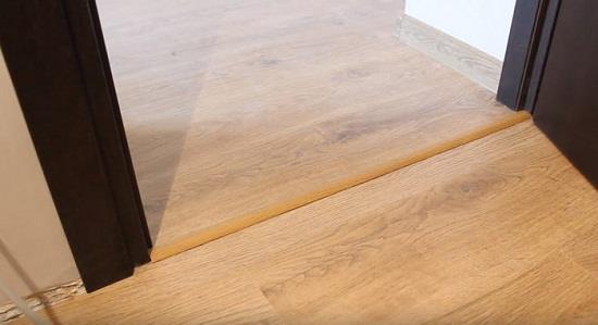 Для соединения напольных покрытий в соседних помещениях используют планку. Она закрывает зазор между покрытиями. Если напольные покрытия имеют один уровень, то применяется одноуровневая планка, если разный, то разноуровневая.