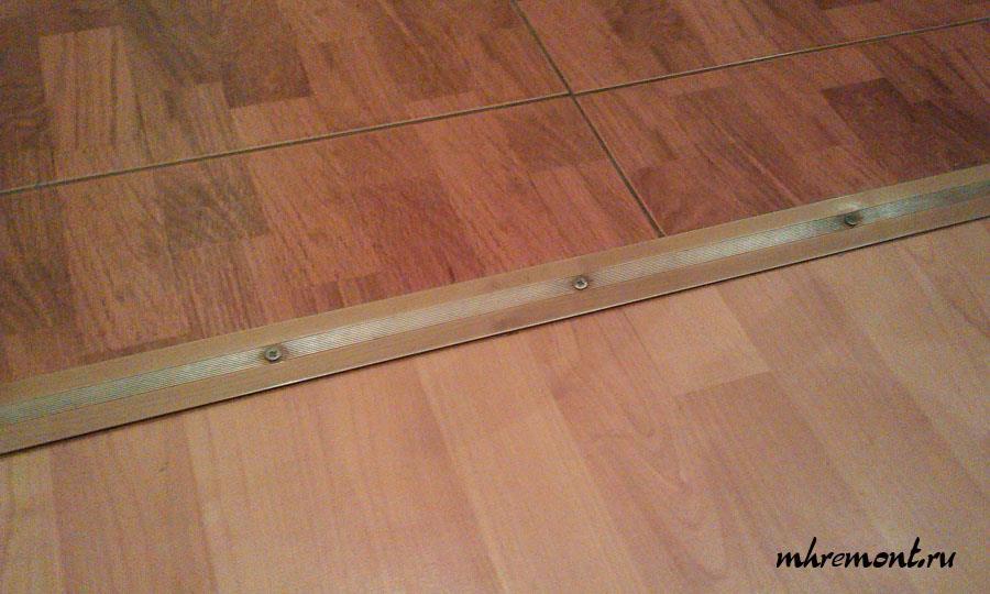 Узкая планка на стыке плитки и ламината.