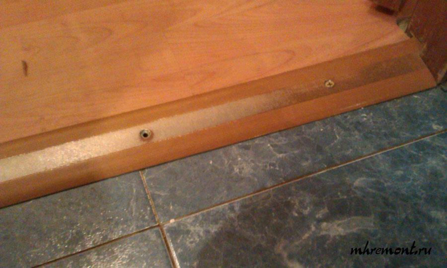Широкая планка на стыке плитки и ламината.