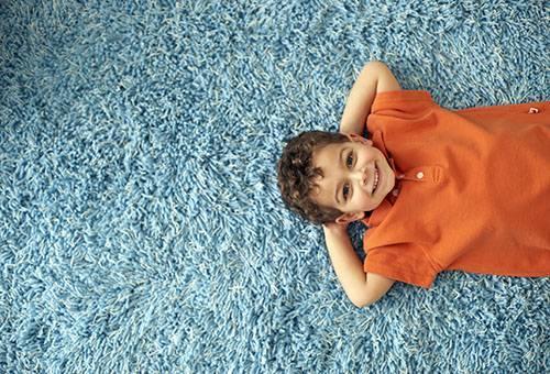 Мальчик лежит на чистом ковре