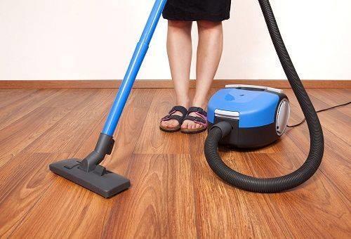 девушка чистит пол пылесосом