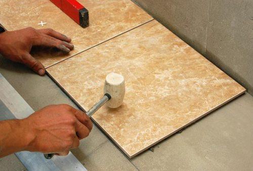 Используем резиновый молоток для выравнивания плитки