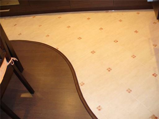 Совмещение двух видов напольного покрытия на кухне давно стало популярным