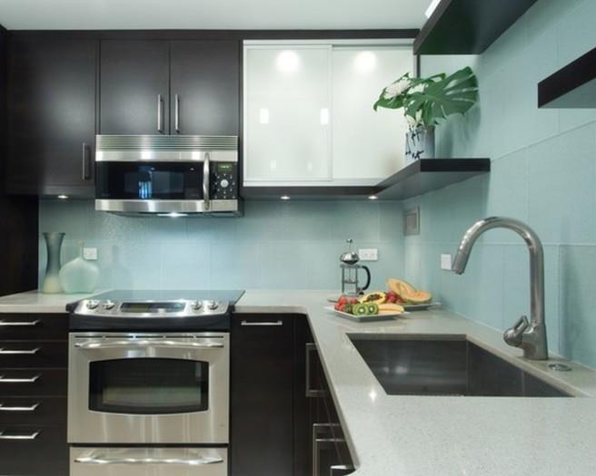 Кухня в строгом стиле: тёмная мебель, много глянца и стали, голубая глянцевая плитка на фартуке.