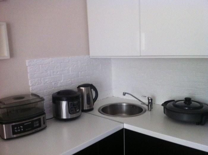Фартук на кухне из гипсовой плитки покрытой защитным лаком. Приготовление пищи происходит в мультиварке.